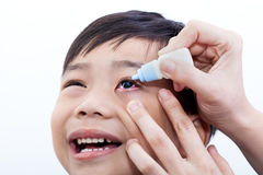父母倾吐的眼药水特写镜头在眼睛的她的儿子 免版税库存照片