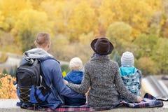 父母和两个儿子看高度黄土  秋天 回到视图 免版税库存图片