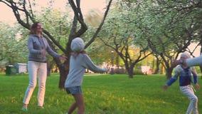 父母和两个女儿在春天公园演奏与球的体育在开花的庭院里 有效的休闲 股票视频
