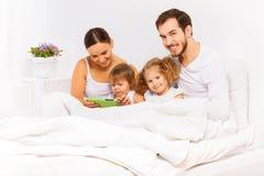 父母和两个孩子使用与在白色床上的片剂 免版税库存照片