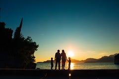 父母和两个孩子剪影海上日落的 Montene 免版税库存图片