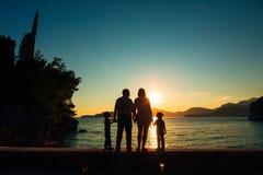 父母和两个孩子剪影海上日落的 Montene 库存图片