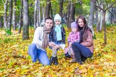 年轻父母和两个孩子在秋天在a停放 免版税库存照片