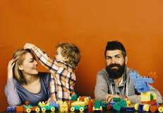 父母和儿子有愉快的面孔的做砖建筑 爱和家庭比赛 年轻家庭花费在游戏室的时间 免版税库存图片