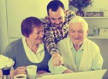 父母和儿子观看的照片 免版税图库摄影