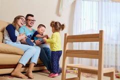 父母和儿童愉快的笑在他们的房子里屋子  库存照片