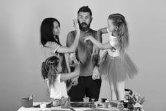 父母和儿童油漆在父亲用树胶水彩画颜料武装 女孩、男人和妇女有微笑和惊奇的面孔的 库存图片