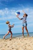 父母和儿童游戏在海岸的一个球在一个夏日 图库摄影