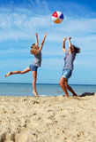 父母和儿童游戏在海岸的一个球在一个夏日 库存照片