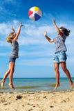 父母和儿童游戏在海岸的一个球在一个晴朗的夏日 库存图片