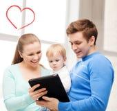 父母和可爱的婴孩有片剂个人计算机的 免版税库存图片