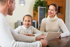 父母和女儿回答问题 免版税库存照片