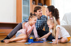 父母和女儿有玩具乐透纸牌的 免版税库存图片