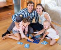 父母和女儿有玩具乐透纸牌的 图库摄影