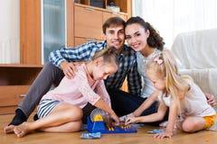 父母和女儿有玩具乐透纸牌的 库存图片
