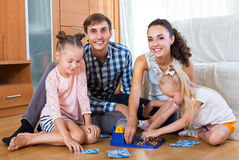 父母和女儿有玩具乐透纸牌的 免版税库存照片