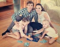 父母和女儿有玩具乐透纸牌的 免版税图库摄影