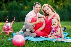 父母和女儿玩具格子花呢披肩背景的  库存照片