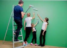 父母和孩子是油漆每新的室 图库摄影