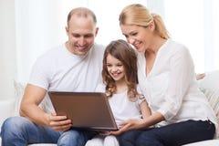 父母和小女孩有膝上型计算机的在家 免版税库存照片