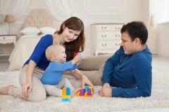 年轻父母和逗人喜爱的儿子在儿童居室演奏大厦成套工具坐一张地毯 免版税库存图片