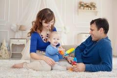 年轻父母和逗人喜爱的儿子在儿童居室演奏大厦成套工具坐一张地毯 免版税图库摄影