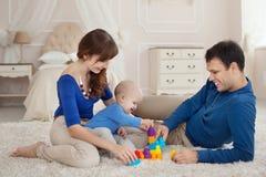 年轻父母和逗人喜爱的儿子在儿童居室演奏大厦成套工具坐一张地毯 图库摄影