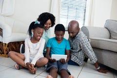 父母和他们的使用数字式片剂的孩子在客厅 免版税库存图片