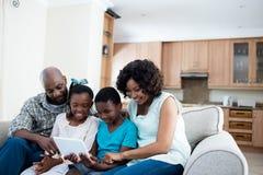 父母和他们的使用数字式片剂的孩子在客厅 图库摄影