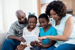 父母和他们的使用数字式片剂的孩子在客厅 免版税库存照片