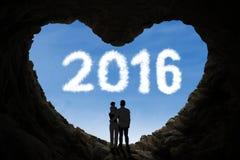 父母和他们的孩子在洞里面与第2016年 库存图片