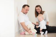 父母和他们美丽的女婴坐地面和使用 库存图片