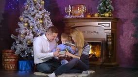 父母在圣诞夜里给他们的男孩一个小礼物打开 影视素材