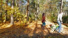 父母在有小孩子的自行车的森林里走 慢的行动 股票视频