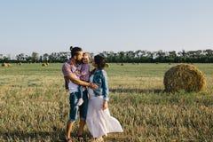 父母在领域拥抱他们的小女儿户外 免版税库存图片