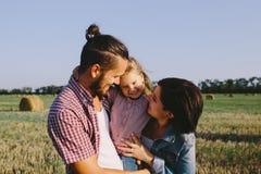父母在领域拥抱他们的小女儿户外 免版税库存照片