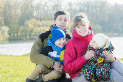 父母家庭成员画象有两兄弟姐妹的在公园 免版税图库摄影
