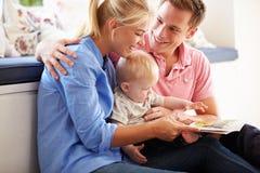 父母对年轻儿子的阅读书 免版税库存照片