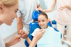父母带来他们的女儿看女孩在牙齿椅子坐的牙医 医生附近站立 免版税库存照片