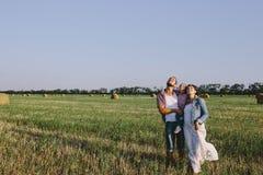 父母拥抱她的小女儿室外在领域 图库摄影