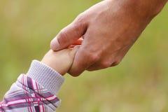 父母握一个小孩子的手 库存照片