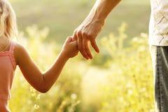 父母握一个小孩子的手 免版税库存照片