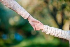 年轻父母握一个小孩子的手 库存照片