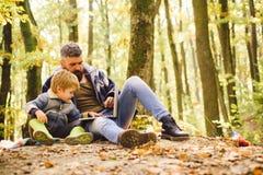 父母教婴孩 使用膝上型计算机的爸爸和儿子公园 使用在秋天森林里的父亲和儿子 库存图片