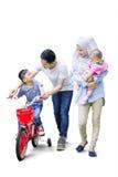 父母教他们的儿子骑自行车 免版税库存图片