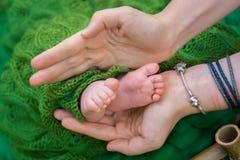 父母的新出生的婴孩脚和手 免版税库存图片