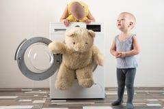 父母被买一台新的洗衣机 孩子设法打开它和洗涤软的玩具 愉快的男孩在家使用 图库摄影