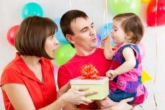 父母被给礼物微笑的儿童女孩 免版税库存照片