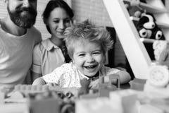 父母观看他们的与五颜六色的块的儿子戏剧 夫妇在有婴孩微笑的客厅 免版税库存图片