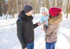 父母身分、季节和人概念-有孩子的愉快的家庭在冬天穿衣户外 免版税库存照片